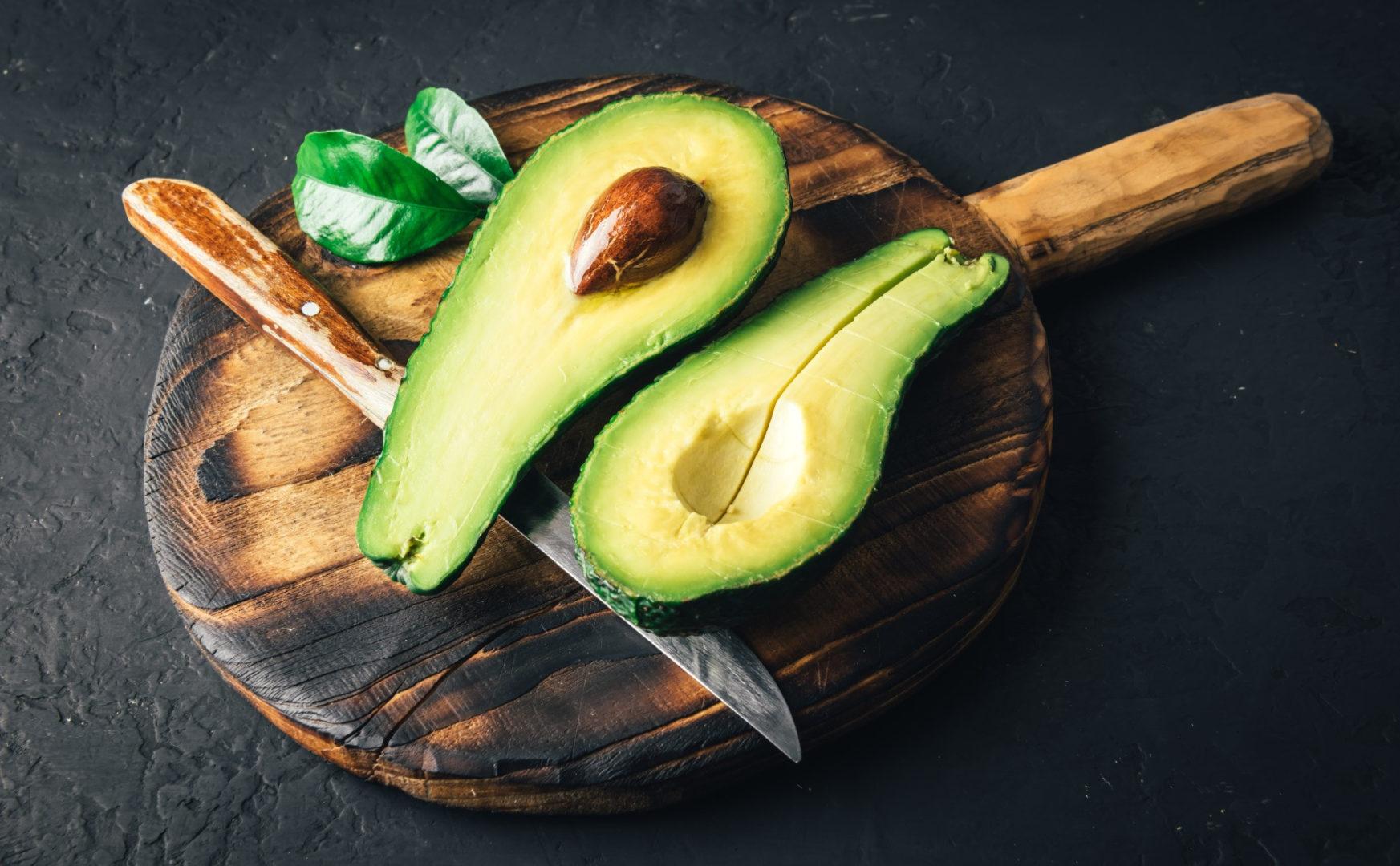 τροφές που ρίχνουν τη χοληστερίνη - fresh avocado fruit on a wooden board - 6+1 τροφές που ρίχνουν τη χοληστερίνη